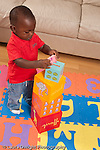 12 month old baby boy standing playing with toys putting toy animal pig on top of stack of blocks concept on top of vertical