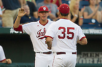 Indiana Hoosiers pitcher Walker Stadler (25) greets teammate Will Coursen-Carr (35) after he completed an inning against the Mississippi State Bulldogs during Game 6 of the 2013 Men's College World Series on June 17, 2013 at TD Ameritrade Park in Omaha, Nebraska. The Bulldogs defeated Hoosiers 5-4. (Andrew Woolley/Four Seam Images)