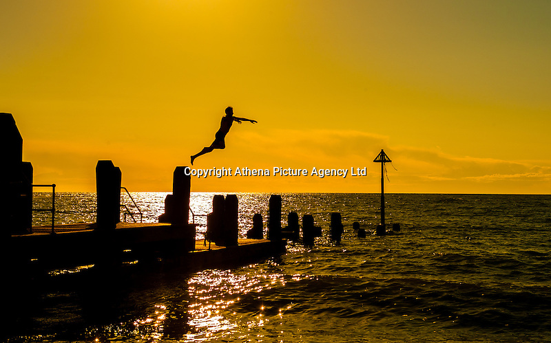 Aberystwyth, West Wales, UK Weather: A young man jumps from the wooden jetty at sunset in Aberystwyth, Wales, UK