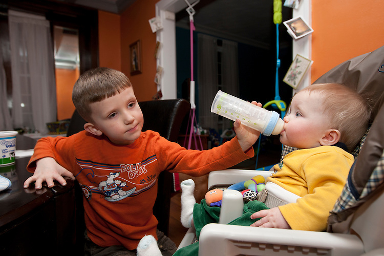 """Benjamin, 5, feeds his little brother Nathan to help out his parents. Their father Matthew said, """"Benjamin has become so helpful we sometimes ask him not to help. We want to make sure he gets to play like a kid should."""""""