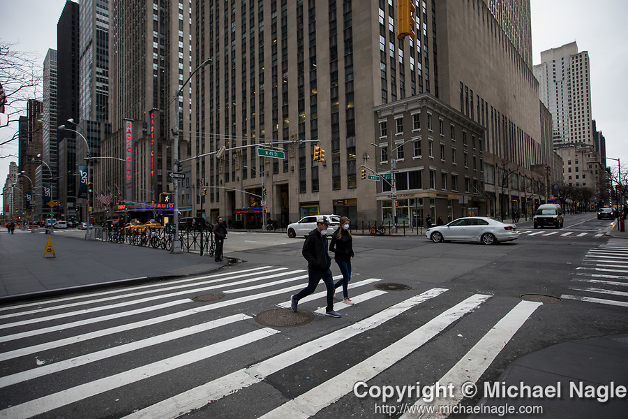 Pedestrians wearing face masks walk along 6th Avenue in New York, U.S., on Thursday, March 19, 2020. New York state Governor Andrew Cuomo on Thursday ordered businesses to keep 75% of their workforce home as the number of coronavirus cases rises rapidly. Photograph by Michael Nagle/Redux