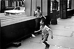MANHATTAN , NEW YORK,  USA  JUNE 1969: YOUNG BOY HOLDS UP AN OPEN KNIFE AS IF TO ATTACK ANOTHER CHILD WHO IS RUNNING AWAY. Two juvenile males play knife blade fight pretend throw terror acting like adults street crime terrorizes fear fun