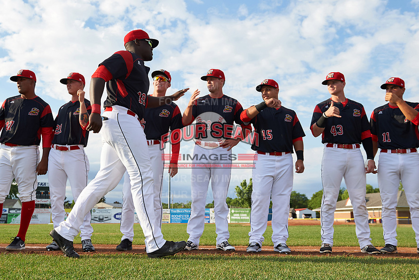 Batavia Muckdogs first baseman Lazaro Alonso (19) greets teammates including Manuel Rodriguez (47), Shane Sawczak (21), Hunter Wells (35), Brent Wheatley (23), Bryan De La Rosa (15), Alex Jones (43), and Mike Garzillo (11) during introductions before a game against the Auburn Doubledays on June 19, 2017 at Dwyer Stadium in Batavia, New York.  Batavia defeated Auburn 8-2 in both teams opening game of the season.  (Mike Janes/Four Seam Images)