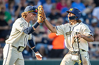 Michigan Wolverines outfielder Jordan Brewer (22) celebrates with teammate Jesse Franklin (7) after scoring against the Vanderbilt Commodores during Game 1 of the NCAA College World Series Finals on June 24, 2019 at TD Ameritrade Park in Omaha, Nebraska. Michigan defeated Vanderbilt 7-4. (Andrew Woolley/Four Seam Images)