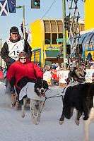 Musher Bob Storey and Iditarider Jedd Smith.leave the 2011 Iditarod ceremonial start line in downtown Anchorage, Alaska