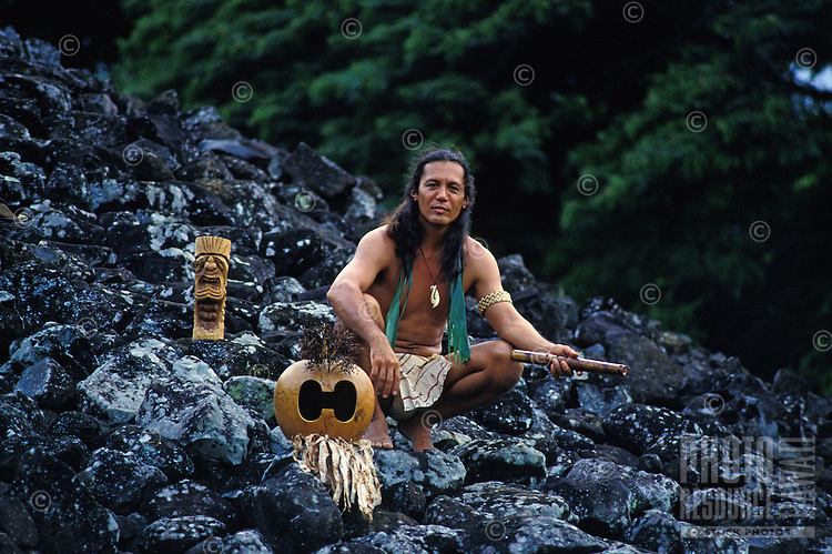 Hawaiian man with native flute and mask at Ulupo temple heiau, Oahu