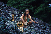 Hawaiian man with native flute and mask at Ulupo temple heiau, Oahu