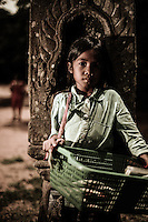 UNESCO World Heritage Site,  Ankgor wat temples . A child  stand in front of a Khmer style bas-relief . Local children  usually make their living by selling crafts and other products to tourists.   Seam Reap, Cambodia.
