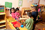 Education preschool 4 year olds two boys aiming long blocks of wood like guns at two girls in pretend play area