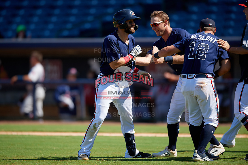 Mississippi Braves Alejandro Salazar (48) is congratulated by teammates Connor Lien (5) and Tyler Neslony (12) after laying down a bunt for a walk-off squeeze play during a Southern League game against the Jacksonville Jumbo Shrimp on May 5, 2019 at Trustmark Park in Pearl, Mississippi.  Mississippi defeated Jacksonville 1-0 in ten innings.  (Mike Janes/Four Seam Images)