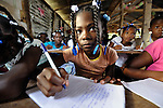Children study in a quake-damaged school building in the rural Haitian village of Embouchure. The Episcopal Church-sponsored school was damaged in the January 2010 earthquake, yet classes have continued inside. In October villagers began holding classes in a large tent while the old building is razed and a new one constructed. The project is sponsored by International Orthodox Christian Charities and FinnChurch Aid.