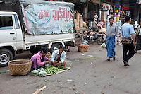 Myanmar, Burma, Mandalay.  Selling Okra in the Street.  Man wearing a traditional longyi, the Burmese wrap-around sarong.