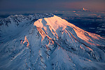 The last light of a winter day illuminates Mt. St. Helens' western face; Mt. Hood appears on the horizon