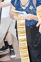 """A woman hands out stickers reading """"Trump/Pence Must Go!"""" as Wayfair employees demonstrate in Copley Square to protest their company's sale of furniture to detainment camps for children operated by US Customs & Border Protection (CBP) on the Mexico border in Boston, Massachusetts, USA, on Wed., June 26, 2019. Wayfair is an online furniture retailer. Employees are asking for the company to set ethics standards for sales. The Wayfair employees were joined by union representatives, PRIDE activists, and other groups in solidarity.  This action occurred the week after US government legal representatives argued that children held in CBP facilities did not need soap or beds to meet the """"safe and sanitary"""" standard of care required by law after months and years of criticism of Trump administration policies of family separation and cruel treatment of those held at its facilities."""