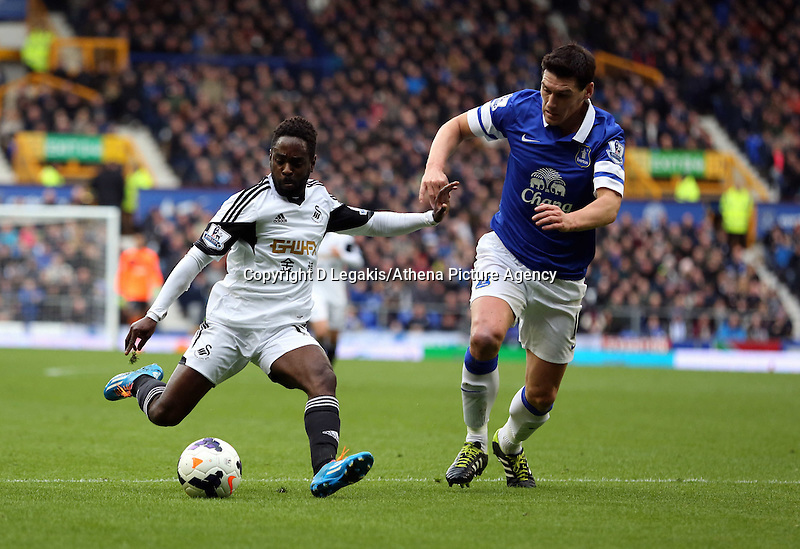 Pictured: Nathan Dyer (L) takes a shot while closely marked by an Everton player. Saturday 22 March 2014<br /> Re: Barclay's Premier League, Everton v Swansea City FC at Goodison Park, Liverpool, UK.