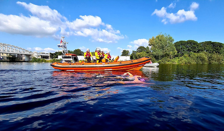 Passing the White Bridge RNLI Lifeboat with swimmers Karen Delaney & Serena Friel (L-R) in the foreground