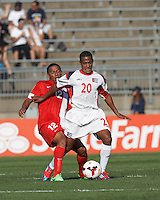Cuban midfielder Alberto Gomez (20) controls the ball as Belize forward Christobal Gilharry (12) pressures. In CONCACAF Gold Cup Group Stage, the national team of Cuba (white) defeated national team of Belize (red), 4-0, at Rentschler Field, East Hartford, CT on July 16, 2013.