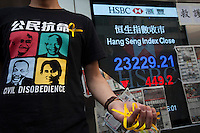 Pro-democracy protester hands out yellow ribbons symbolising democracy as a sign board shows Hong Kong's stock market Hang Seng Index falling by 449.2 points, in Mong Kok, on the second day of the mass civil disobedience campaign Occupy Hong Kong, Mong Kok, Kowloon, Hong Kong, China, 30 September 2014. The movement is also being dubbed the 'umbrella revolution' after the versatile umbrellas used to shield protesters from rain, sun - and police pepper spray.