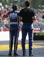 Mar. 16, 2013; Gainesville, FL, USA; NHRA pro stock motorcycle rider Hector Arana Sr (left) shows son Adam Arana the track conditions during qualifying for the Gatornationals at Auto-Plus Raceway at Gainesville. Mandatory Credit: Mark J. Rebilas-