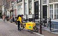 Nederland  Amsterdam -  2020. DHL koerier in het centrum van Amsterdam. Foto : ANP/ HH / Berlinda van Dam