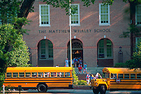 School busses lined up in front of a school building.
