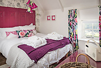 BNPS.co.uk (01202) 558833<br /> Pic: LillicrapChilcott/BNPS<br /> <br /> Vine Cottage a rare property in the tiny fishing cove of Cadgwith Cornwall<br /> <br /> A chocolate box thatched cottage perched on a cliff with views out to sea is on the market for offers over £1.1m.<br /> <br /> The beautiful Grade II listed property sits on the cliff above the fishing village of Cadgwith, Cornwall, just a short walk from the cove and beach.<br /> <br /> The former fisherman's cottage is currently split into two adjoining cottages that have been let as holiday homes and produced a very lucrative income.<br /> <br /> But the two-bedroom and one-bedroom cottages could be integrated together again to make a larger family home.