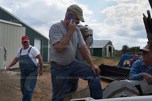 Lowell, Arkansas<br /> Transmission trouble stalls work at some of the chicken houses that George Anderson (with cell phone) operates. Farmer Rick Harriman, left, hauls chicken manure, valuable fertilizer, and spreads in on surrounding pastures. He receives $45.00 per truckload as well as $4.00 a mile for his labor. With over 150 cattle, Rick keeps some of the manure for his own pastures; it is less costly and longer lasting than commercial fertilizer.