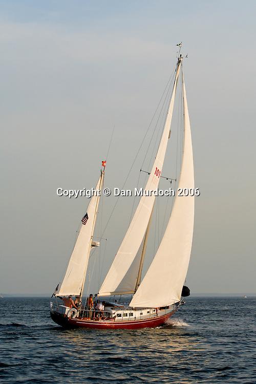 Ketch sailboat sailing into setting sun