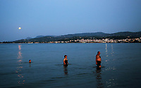 A full moon with a partial eclipse, rises while people cool off in the sea in Oropos in the Evia Bay, 30 miles east of Athens, Greece. Monday 07 August 2017