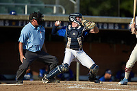 Martinsville Mustangs catcher Matthew Suggs (1) (UNC Wilmington) pops up to make a throw as home plate umpire Brian Pitts looks on during the game against the High Point-Thomasville HiToms at Finch Field on July 26, 2020 in Thomasville, NC.  The HiToms defeated the Mustangs 8-5. (Brian Westerholt/Four Seam Images)