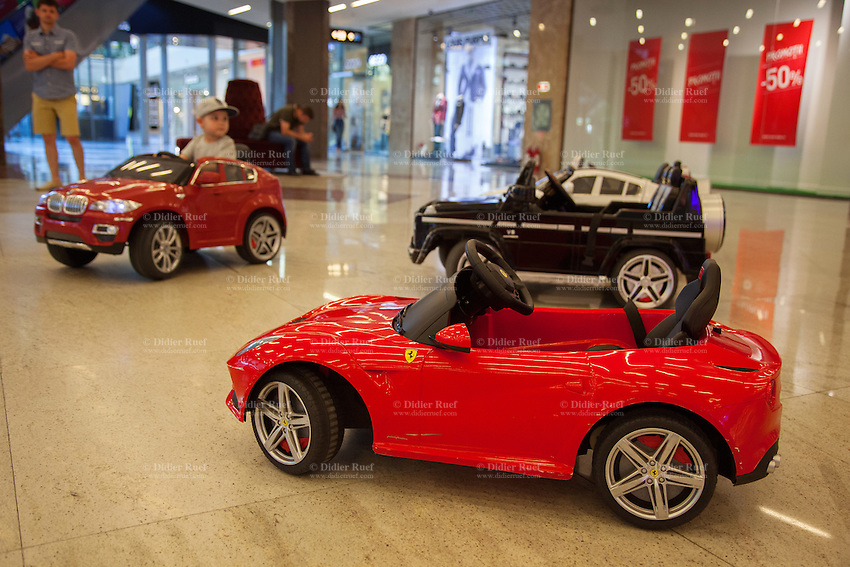 Romania. Iași County. Iasi. Town center. Palas Mall. A young boy drives an electric battery BMW X6 SUV / Remote Control operated ride on car while his father looks at him and waits for him. Other cars for rent, such as Ferrari F12 Berlinetta, the stunning fully licensed Mercedes AMG G55 Luxury Kids 12v Jeep or the luxury sports BMW i8 Concept Electric Ride-On Car. The small private business offer customers the opportunity to rents cars detailed and to scale replica of the road. Parents can pay for their children a five to ten minutes ride in the Palas Mall. Iași (also referred to as Iasi, Jassy or Iassy) is the largest city in eastern Romania and the seat of Iași County. Located in the Moldavia region, Iași has traditionally been one of the leading centres of Romanian social life. The city was the capital of the Principality of Moldavia from 1564 to 1859, then of the United Principalities from 1859 to 1862, and the capital of Romania from 1916 to 1918. 6.06.15 © 2015 Didier Ruef