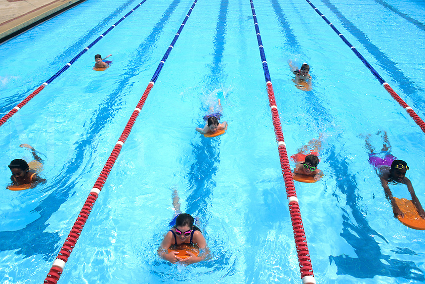 Mixed ethnic group of children in swimming lanes learning to swim and compet