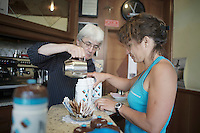 an AG2R-LaMondiale soigneur gets her hot wather for tea at the local bar (the riders get it if they are confronted with cold conditions during the stage)<br /> <br /> 2014 Giro d'Italia<br /> stage 18: Belluno - Rifugio Panarotta (Valsugana), 171km
