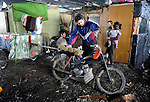 Arden Dasi, preparing his motorcycle and recycling cart, lived under a bridge in a Roma settlement in Belgrade, Serbia, when this photo was taken iin February 2012. He is a refugee from Kosovo. The families that lived here, most of whom survive from recycling cardboard and other materials, were forcibly evicted in April 2012. Many were moved into metal shipping containers on the edge of Belgrade..