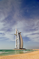 Burj al Arab Hotel, an icon of Dubai built in the shape of the sail of a dhow, stands on an artificial island just off Jumeirah Beach.  Dubai. United Arab Emirates. Architects W.S. Atkins.