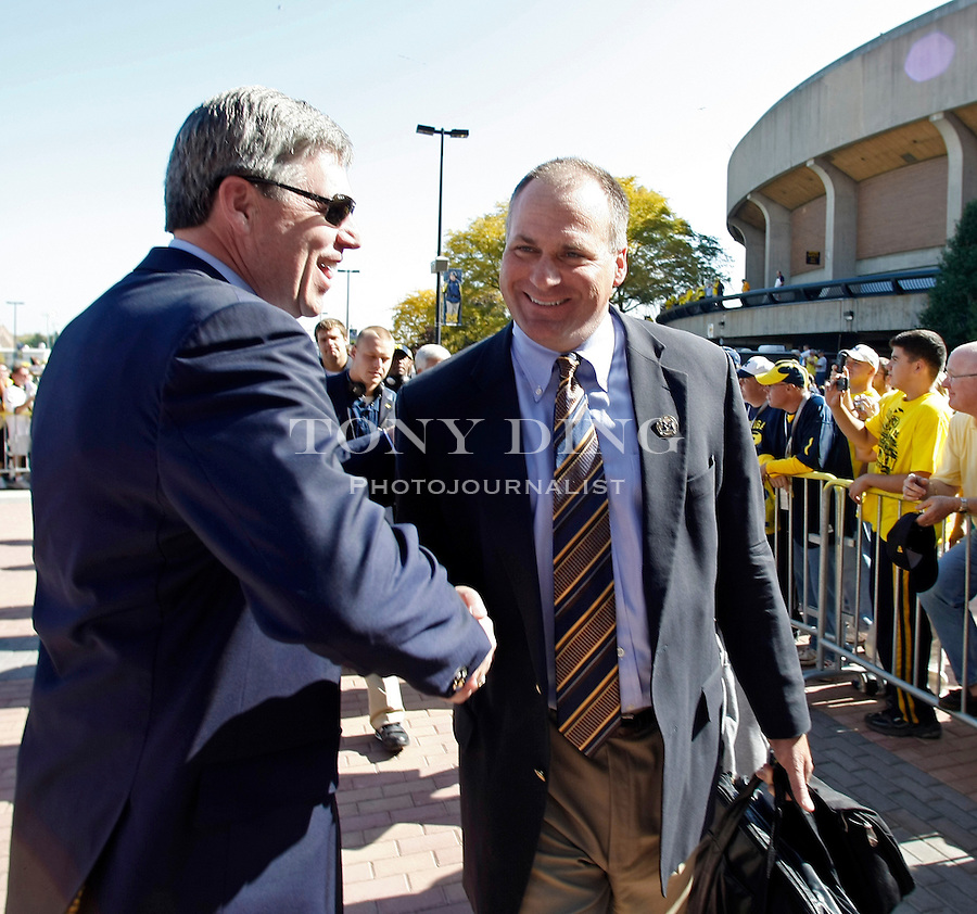 Michigan Athletic Director David Brandon, left, shakes hands with head coach Rich Rodriguez as they arrive at Michigan Stadium before an NCAA college football game with Michigan State, Saturday, Oct. 9, 2010, in Ann Arbor, Mich. (AP Photo/Tony Ding)