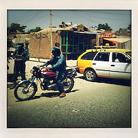 An Afghan policeman on a motorbike stops to talk to a colleague on a busy Kabul street.