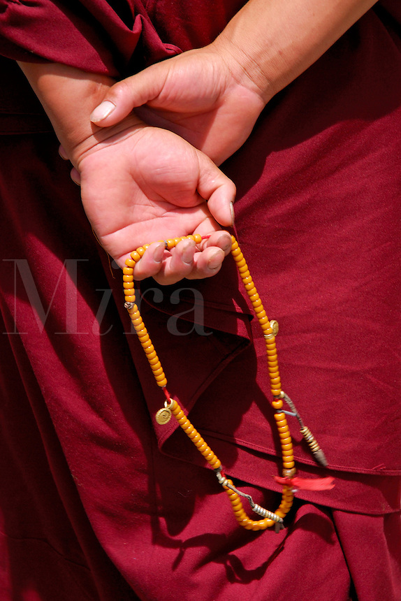 Tibetan Buddhist monk counting with mala, or rosary beads, while walking the Barkhor pilgrim circuit around the Jokhang Temple, Lhasa, Tibet.