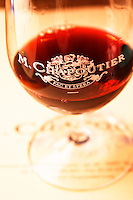 A glass of red Hermitage with inscription M Chapoutier Fac et Spera against a white background in the tasting room. Domaine M Chapoutier, Tain l'Hermitage, Drome Drôme, France Europe