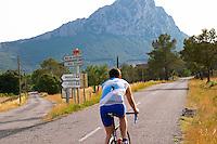 Mas de la Plaine, Mas Rigaud, Mas Bruguiere, Domaine de l'Hortus. A man on bicycle. The Pic St Loup mountain top peak. Pic St Loup. Languedoc. France. Europe.