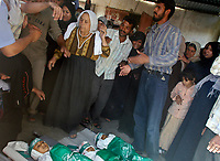 """Palestinians try to comfort a woman as she mourns during the funeral of four children and their mother from the Abu Maateq family in Beit Hanun, in the Gaza Strip on April 28, 2008. Four children, aged one to five, their mother and a militant were killed in Israeli operations in Gaza today as Palestinian factions headed to Egypt for talks on a possible truce. The four siblings -- aged one, three, four and five -- were killed when a tank shell hit their home in the town of Beit Hanun, and their mother died later of her wounds, doctors at the Kamal Radwan hospital said.""""photo by Fady Adwan"""""""