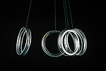 A canning jar lid ring photographed as multiple exposure while swinging on string against black background.