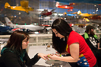 Rin Venieris of Seattle gets her nails painted with Captain Marvel icons by Christal VanEtten of Espionage Cosmetics in Bellingham during the Carol Corps Celebration Thursday March 27, 2014 at the Museum of Flight in Seattle. Held the day before Emerald City Comicon kicked off, the event raised funds for Girls Leadership Institute and offered a chance for fans to meet and chat with Captain Marvel writer Kelly Sue DeConnick and Ms. Marvel writer G. Willow Wilson. Photo by Daniel Berman for WIRED.com