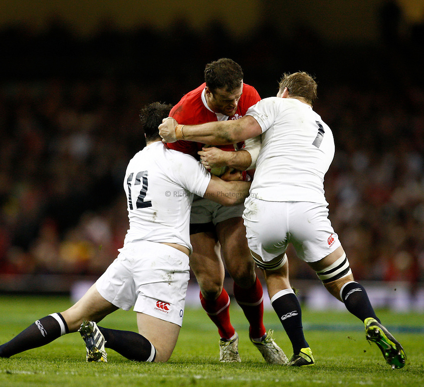 Photo: Richard Lane/Richard Lane Photography. Wales v England. RBS 6 Nations Championship. 16/03/2013. Wales' Jamie Roberts is tackled by England's Brad Barritt and Chris Robshaw.