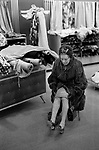 Derry and Toms, Fashionable middle aged older woman  shopping and tired wearing a fur coat in the fabric department of a large London department store London UK 1971 1970s.