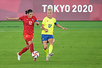 YOKOHAMA, JAPAN - AUGUST 6: Christine Sinclair #12 of Canada battles for the ball with Caroline Seger #17 of Sweden during a game between Canada and Sweden at International Stadium Yokohama on August 6, 2021 in Yokohama, Japan.