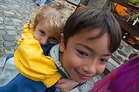 Young boy carrying his cousin on his back, Brittany, France.