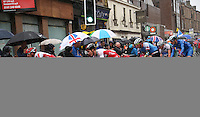 Sunday 3rd August 2014<br /> Pictured: Commonwealth Games Men's Road Race<br /> RE: Men's road race cyclists on Byres Road, Glasgow, Scotland, competing in the Commonwealth Games 2014, spectators with umbrellas.