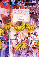 Apple bananas hanging on display at a Chinatown food market in front of Asian posters, Honolulu