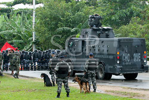 Army shock troops with an armoured troop carrier and dogs face demonstrators - indigenous people, the Landless People's Movement (MST) and other civil society groups - in front of the Riocentro United Nations conference. The demonstrators are kept out of earshot and invisible to the UN conference. The United Nations Conference on Sustainable Development (Rio+20), Rio de Janeiro, Brazil, 20th June 2012. Photo © Sue Cunningham.